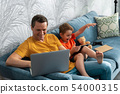 Happy father and son sitting room and using gadgets 54000315