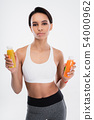 Young fitness lady holding two smoothie drinks 54000962