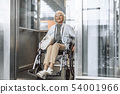 Mature lady in glasses on disabled carriage using elevator 54001966