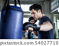 Handsome young man boxer is exercising with a 54027719