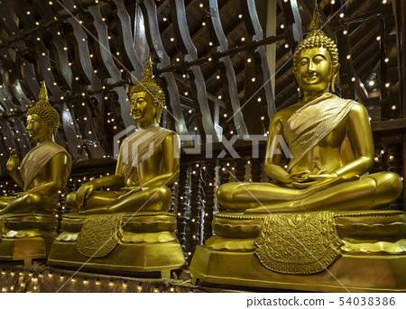 Row of Three Golden Buddha Statues Sitting on Pillows in Seema Malaka Temple 54038386