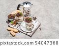 Classic tiramisu dessert in a glass and coffee makeron concrete background 54047368