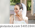 bride talking with her friend in smartphone 54053944