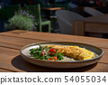 Breakfast. Omelet with tomatoes, arugula, cheese on a blue plate. Frittata - Italian omelette. 54055034