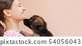 Puppy is giving a kiss to its girl owner 54056043