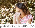 Young pretty girl blowing nose in front of tree. 54056055