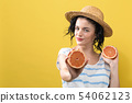 Happy young woman holding oranges 54062123