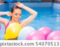 Woman having fun with balloons in water pool 54070513