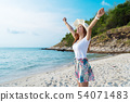 woman wearing hat with arms raised standing on sea 54071483