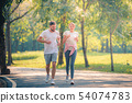 Portrait of Young couple running in the park at 54074783