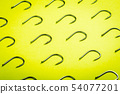 lots of fishing hooks on yellow background  54077201