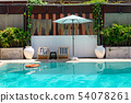 Wooden sunbeds with parasol on swimming pool 54078261