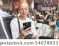 Female traveler reading on her cell phone while waiting to board a plane at departure gates at 54078933