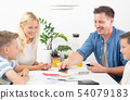 Happy young family playing card game at dining table at bright modern home. 54079183