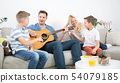 Happy caucasian family smiling, playing guitar and singing songs together at cosy modern home 54079185