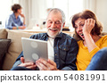 Senior couple using tablet in community center club. 54081991