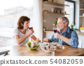 Senior couple with wine having lunch indoors at home, talking. 54082059