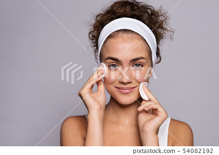 Portrait of a young woman cleaning face in a studio, beauty and skin care. 54082192