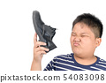 Disgusted boy holding a pair of smelly leather 54083098
