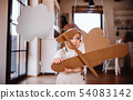 A toddler girl with carton plane playing indoors at home, flying concept. 54083142