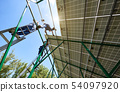 team of young mounters working with solar panels screen. 54097920
