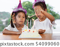 Two girls lighting candle on birthday cake 54099060