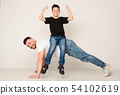 Dad doing push ups with son on back 54102619