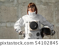 Beautiful girl astronaut without a helmet on the background of a gray wall. Fantastic space suit. 54102845