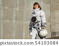 Beautiful girl astronaut without a helmet on the background of a gray wall. Fantastic space suit. 54103084