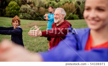 Large group of fit and active people doing exercise in nature, stretching. 54106971