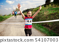 Small girl runner crossing finish line in a race competition in nature. 54107003