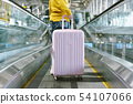 Woman traveler carry big suitcase on escalator 54107066