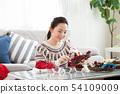 ผู้หญิงกำลังทำพวงหรีดคริสต์มาส 54109009