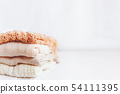 Pile of beige woolen clothes on a white background 54111395