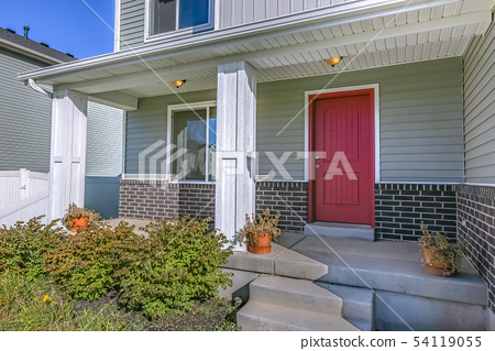 Red front door of a home with porch and stairs 54119055