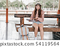 woman traveler with mobile smart phone & map at train station. Travel journey trip concept 54119564