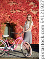 Attractive blond girl at pink lady bicycle on sunny day on wall overgrown with red ivy background. 54121927