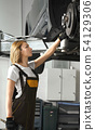 Woman looking at tire of car in auto service 54129306