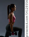 Side view of athletic young girl doing squat exercises 54129356