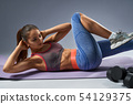 Tanned young athletic girl doing abs workout on yoga mat 54129375
