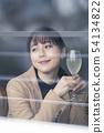 여자 여행에서 조용한 레스토랑에 들어가 와인 잔에 술을 기울 온화한 표정을 짓는다 섹시한 여성 54134822