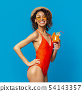Happy african millennial woman in swimwear posing with fresh cocktail 54143357