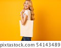 Millennial Woman With Cotton Bag Over Yellow Background 54143489