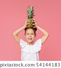 Cute little girl holding fresh pineapple on head 54144183