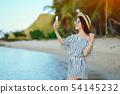 girl waking along the beach using her phone 54145232
