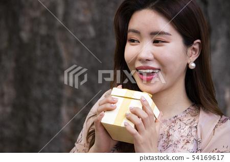 노란선물 박스를 들고 기뻐하는 여성 54169617