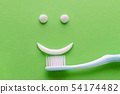 a face with smile from white toothpaste, teeth care concept, toothbrush on green background 54174482