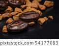 Coffee beans and instant coffee granules on a dark 54177093