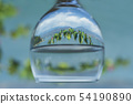 Glass of water with closeup on ocean and mountain nature blur background 54190890