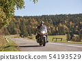 Biker in black leather outfit driving modern powerful motorcycle along sunny road on summer day. 54193529